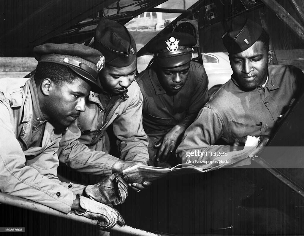 Field Artillery Officers and Tuskegee Airmen Elwood A Smith, Scott K Cleage, Sterling K Jackson and Wendel Long complete pre flight checks on an aircraft before a cross country flight, Tuskegee, Alabama, 1943.