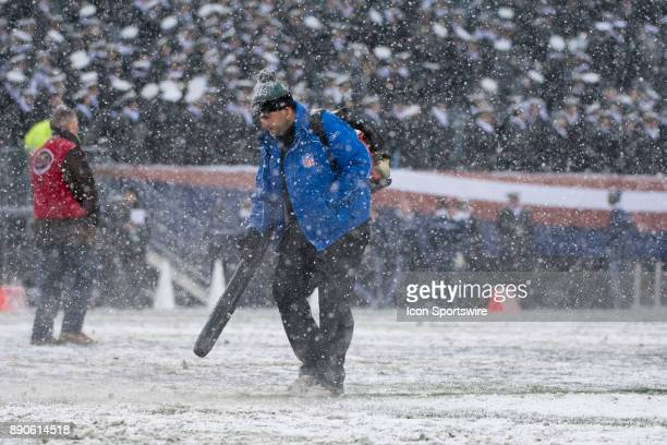 A field crew member blows snow off of the yard lines before the game between The Army Black Knights and Navy Midshipmen on December 09 2017 at...