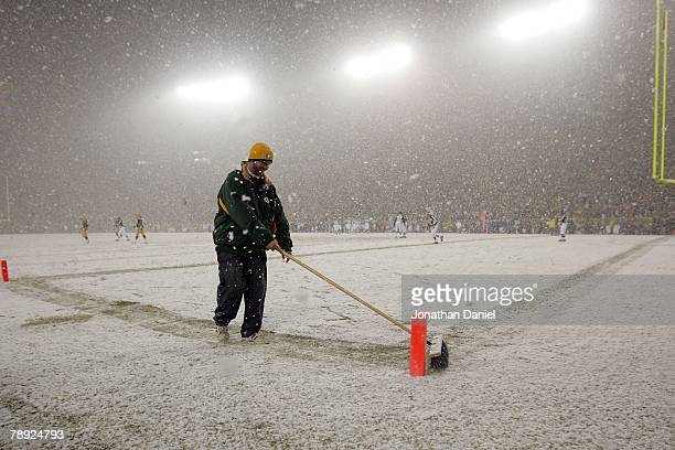 Field crew member sweeps the snow in the endzone during the game between the Green Bay Packers and the Seattle Seahawks during the NFC divisional...