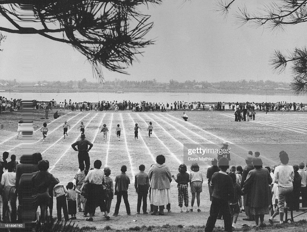 MAY 19 1961; Field Day In A Frame; Effectively framed by pine trees ...
