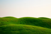 A field full of green grass and hills