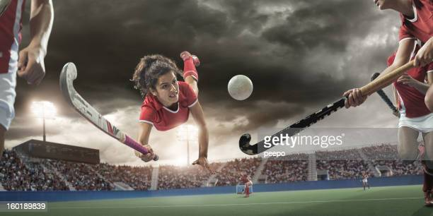 field hockey player diving to hit ball - hockey stock pictures, royalty-free photos & images