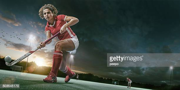 field hockey player in mid action during hockey game - hockey stock pictures, royalty-free photos & images
