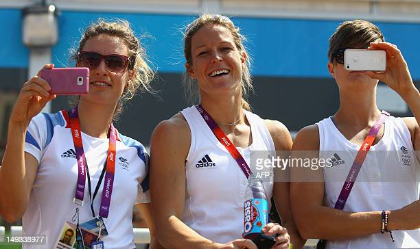 Field hockey players Ashleigh Ball, Crista Cullen and Sally Walton of Great Britain look on during the Olympic Village arrivals ahead of the London...