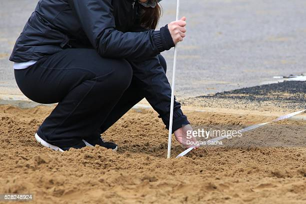 Field Judge Measuring the distance in the sand pit