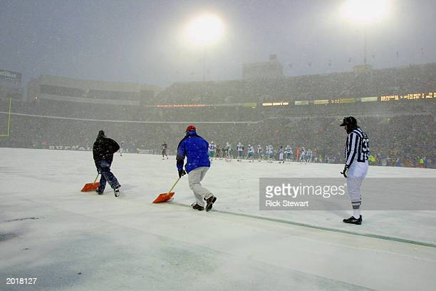 Field Judge Steve Zimmer watches as two Ralph Wilson Stadium ground crew shovel the sideline boundary in the fourth quarter of the Buffalo Bills and...