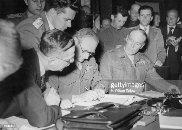 Field Marshal Bernard L Montgomery signing the four power pact regarding the defeat of Germany Allied Supreme Commander Dwight D Eisenhower Marshal...