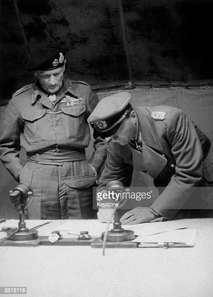 Field Marshal Bernard L Montgomery watches General Kienzl Chief of Staff to Field Marshal Busch sign the surrender of the German land sea and air...