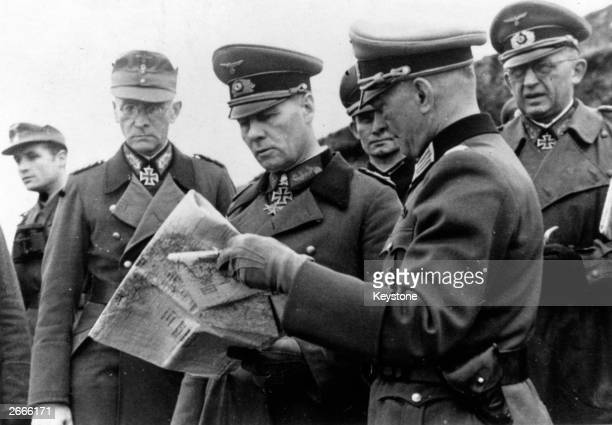 Field Marshal Erwin Rommel centre studies a map with other German army officers at Caen France during an inspection tour of coastal defences