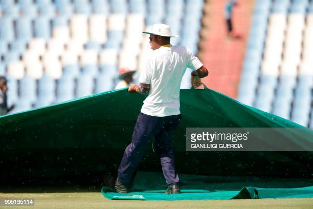 A field marshal pulls a cover over the pitch as the macth is stopped due to rain during the third day of the second Test cricket match between South...