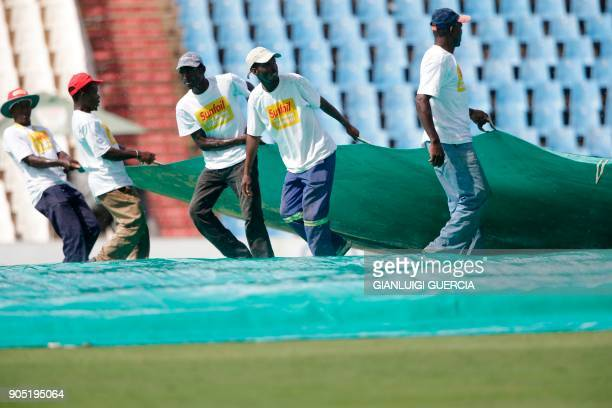 Field marshals pull a cover over the pitch as the macth is stopped due to rain during the third day of the second Test cricket match between South...