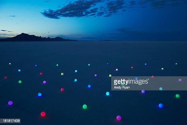 Field of glowing orbs in desert at dusk.