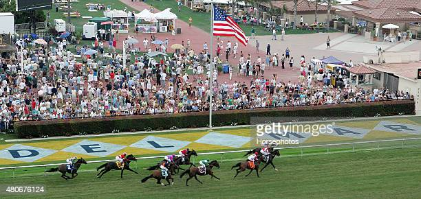 Field of horses pass in front of grandstand and a packed infield crowd at Del Mar Race Track July 20 2005