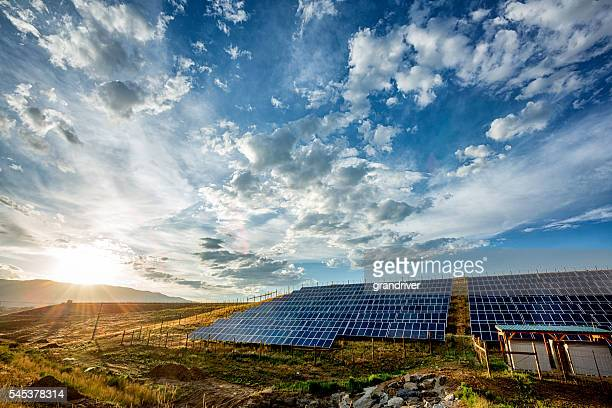 field of solar panels in a rural setting - suns stock photos and pictures
