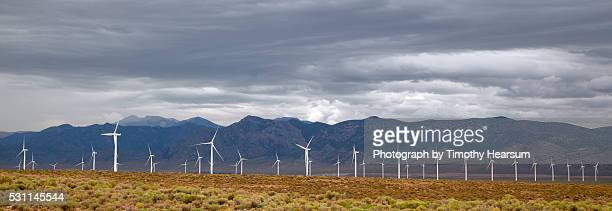 field of wind generators with mountains and stormy sky beyond - timothy hearsum stock pictures, royalty-free photos & images