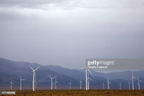 field of wind generators with stormy sky beyond - timothy hearsum stock pictures, royalty-free photos & images