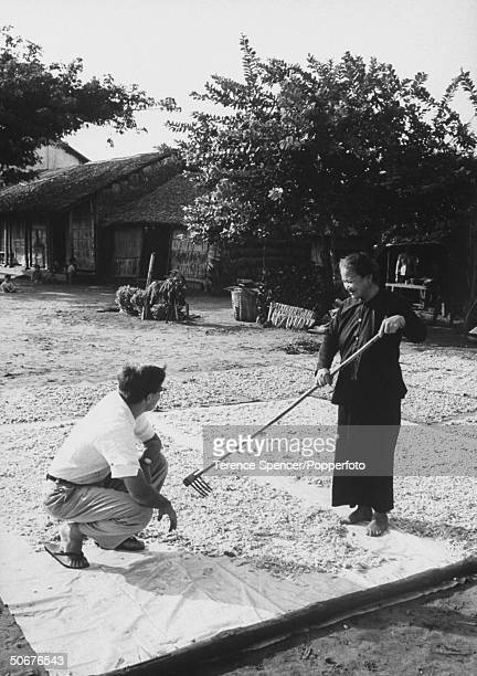 Field Officier, W. Robert Warne , with Vietnamese woman drying shrimp on plastic sheet provided by US.