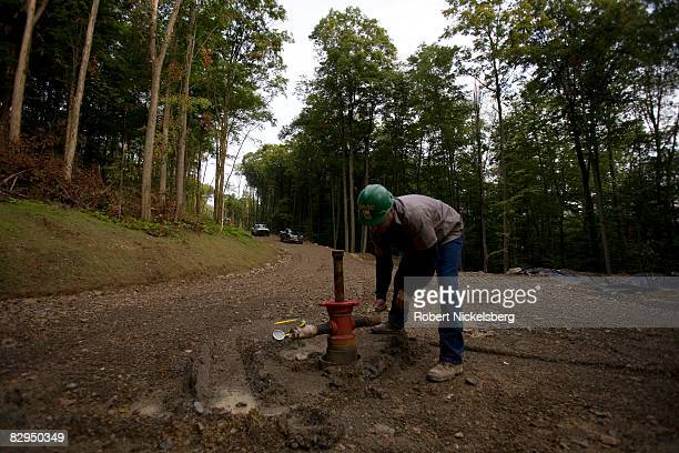 A field representative for Minard Run Oil Company removes a cap from a recently drilled oil well allowing a computerized logging procedure to start...