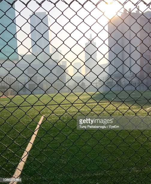 field seen through chainlink fence - wire mesh fence stock pictures, royalty-free photos & images