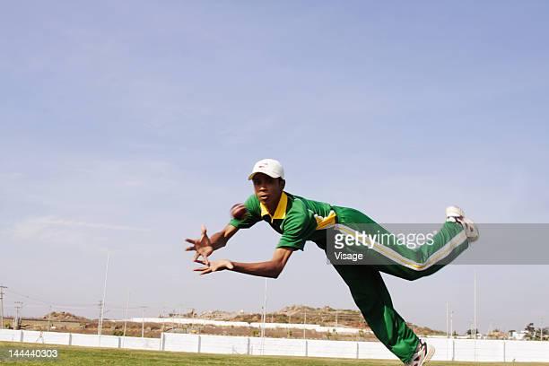 A fielder catching a cricket ball