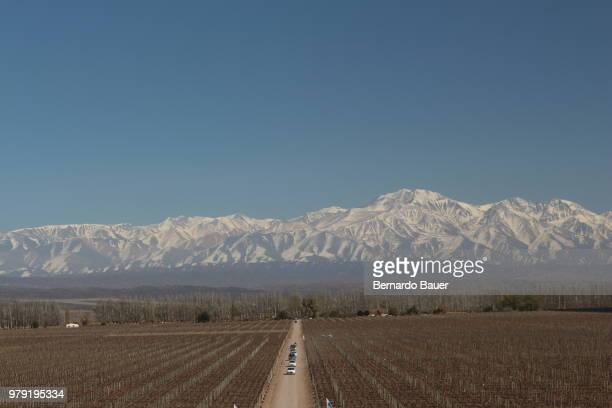 Fields, cars on road and mountains, Mendoza, Argentina