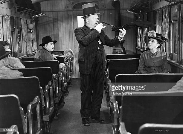 WC Fields shows Margaret Hamilton a bent umbrella in a scene from the film 'My Little Chickadee' directed by Edward F Cline for Universal 1940