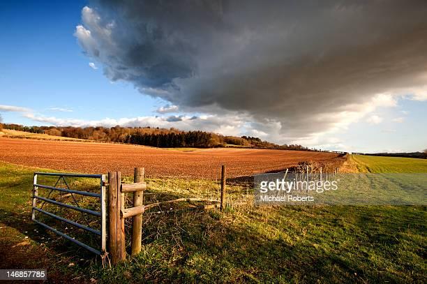 Fields under dark rain cloud
