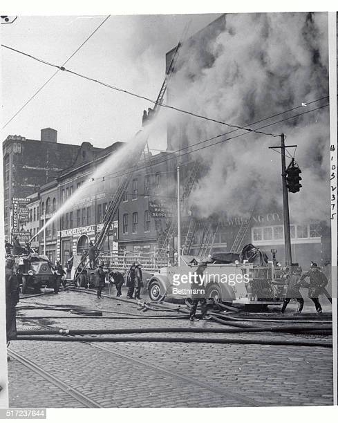 Fiemen are pouring streams of water from thirty hoselines into the building of the William H Whiting Company in Baltimore at the height of the fire...