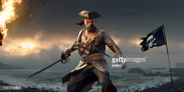 fierce pirate standing on beach with cutlases and jolly roger - pirate stock photos and pictures