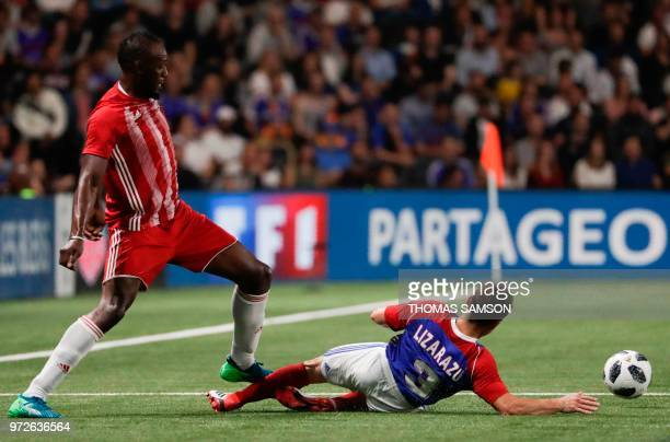 TOPSHOT Fifa 98's Usain Bolt is tackled by France 98's defender Bixente Lizarazu during an exhibition football match between France's 1998 World...