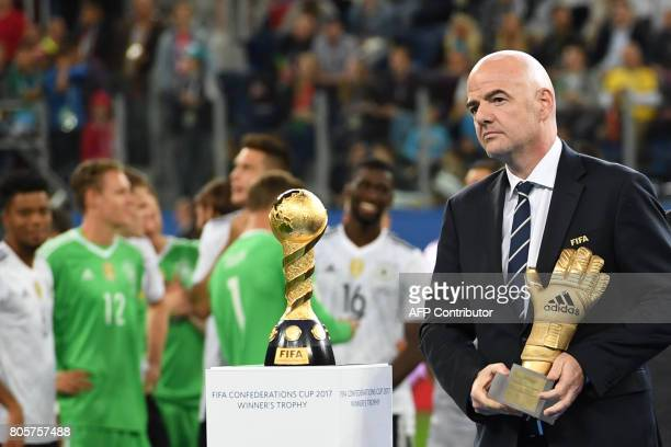 Fifa President Gianni Infantino holds the Golden Glove trophy as he stands next to the winner's trophy during the awards ceremony after Germany beat...
