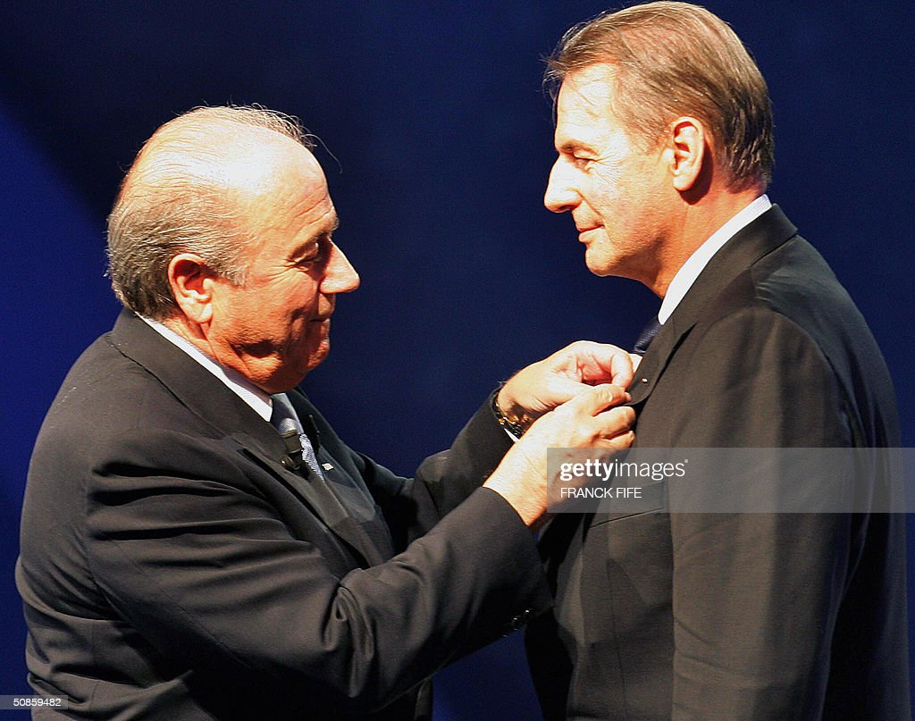 Fifa President Joseph Blatter awards CIO President Jacques Rogge with a 'medaille du merite' (a French merit award) during FIFA's centenary congress, 20 May 2004 in Paris.