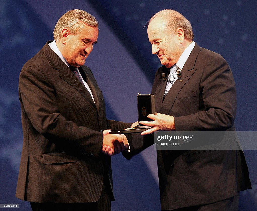 Fifa President Joseph Blatter (R) gives a medal to French Prime minister Jean-Pierre Raffarin (L) during FIFA's centenary congress, 20 May 2004 in Paris.