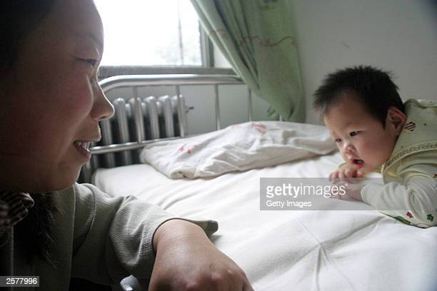 Fifteen month old QingQing lies on her bed while her guardian watches on at the Dongzhimen Hospital October 10 2003 in Beijing China QingQing was...