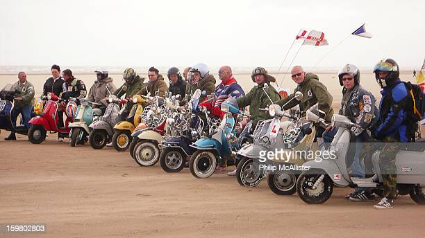 CONTENT] Fifteen scooterists line up on their scooters on a beachThey are in a line and it is windy