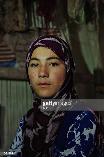 Fifteen year old Afghan girl Ayesha poses at her home in Jowzjan Sheberghan Province some 50kms northwest of MazareSharif on November 16 2012 A young...