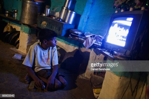 Fifteen year old Sachin Kumar watches television in his home located in a slum near the site of the deserted Union Carbide factory on November 30...