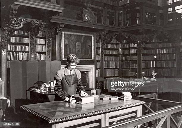 A fifteen yearold volunteer library assistant at work cleaning books in the library of St Paul's Cathedral London 30th December 1950 Original...