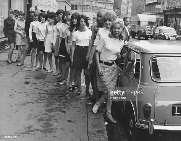Fifteen young women in mini skirts wait to board a BMC Mini outside University Motors in Conduit Street London 21st July 1966 They are about to break...