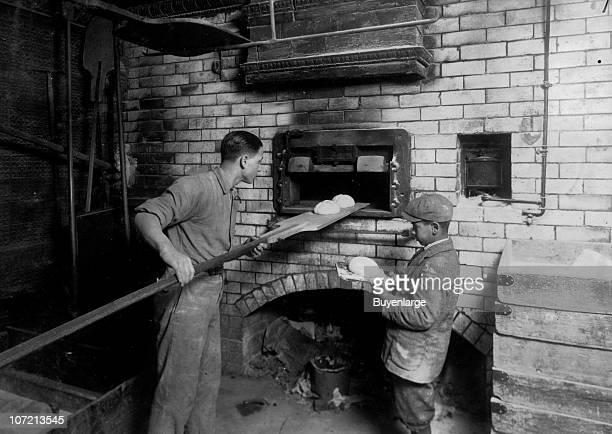 Fifteenyearold Vincenzo Messina and his elevenyearold brother Angelo bake bread in their father's bakery Cambridge Massachusettes 1917