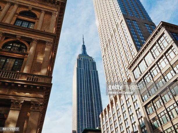 fifth avenue with empire state building in the center, manhattan, new york, ny, united states - empire state building stock pictures, royalty-free photos & images