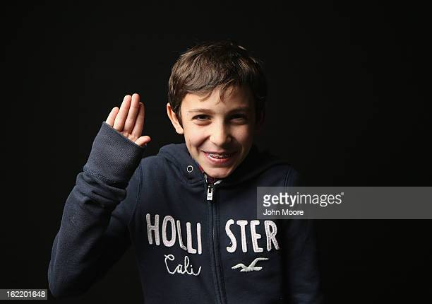Fifth grader Theodore Poncet born in France holds his hand as for the oath of allegiance while awaiting his American citizenship certificate at the...