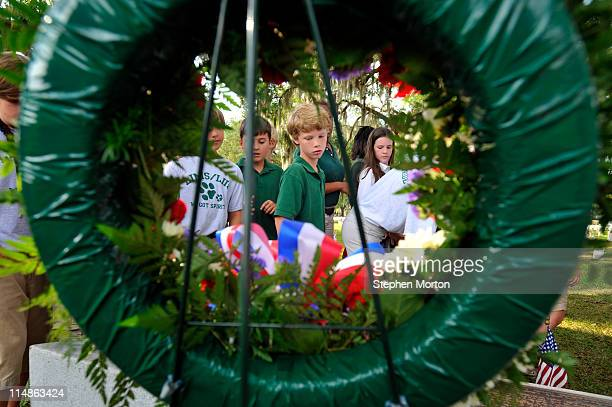 Fifth graders from the Lady's Island Intermediate School walk past a wreath and plaque at the Beaufort National Cemetery marking the mass grave of 19...