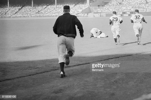 Fifth inning casualty rightfielder Mickey Mantle lies in a heap on the sod as Joe DiMaggio bends over him when Mantle collapsed with an injured knee...