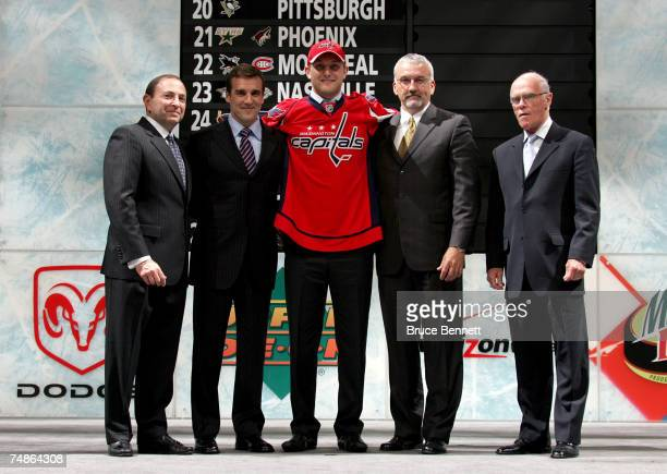 Fifth overall pick Karl Alzner of the Washington Capitals poses with team personnel after being drafted in the first round of the 2007 NHL Entry...