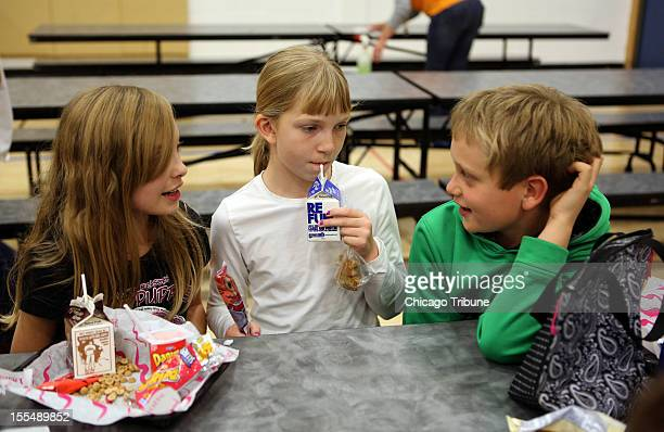 Fifth-graders, from left, Ashley Winter, Jill Jackson and Nate Castagna finish their lunchtime together, October 31 at Western Avenue School in...