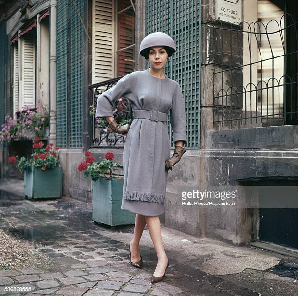 Fifties Fashion A young female model wears a bluegrey wool dress with a wide belt of the same fabric marking a raised waistline with a fringed panel...