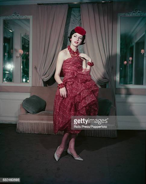 Fifties Fashion A young female model wears a short evening dress fashioned in chiffon with a rusted paisley pattern many stranded necklace with twin...