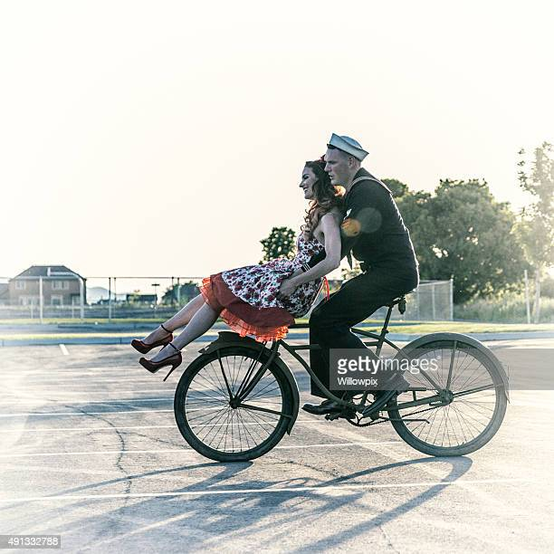 Fifties Navy Sailor Giving Pin Up Girlfriend Ride on Bicycle