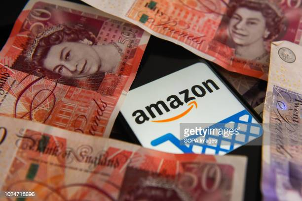 Fifty and twenty pounds bank notes and amazon logo are seen in this photo illustration.